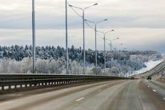 Winter highway with coniferous woodland around. Winter road with Coniferous woodland around in blue tones Stock Image