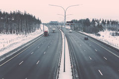 Winter highway with trucks and cars among winter forest. Vintage style toned Royalty Free Stock Photos