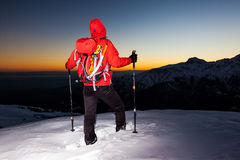 Winter hiking: man stands on a snowy ridge looking at the sunset Stock Photos