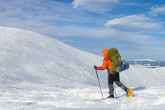 Winter hiking in the mountains on snowshoes with a backpack and tent. Royalty Free Stock Photos