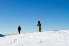 Winter hiking in the mountains on snowshoes with a backpack and tent. Royalty Free Stock Photography