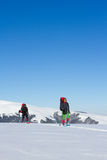 Winter hiking in the mountains on snowshoes with a backpack and tent. Royalty Free Stock Image