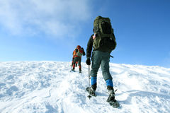 Winter hiking in the mountains on snowshoes with a backpack and tent. Stock Photos