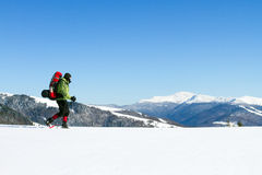 Winter hiking in the mountains on snowshoes with a backpack and tent. Royalty Free Stock Photo