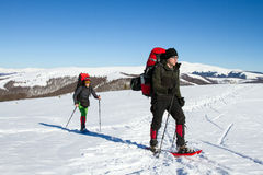 Winter hiking in the mountains on snowshoes with a backpack and tent. Royalty Free Stock Images