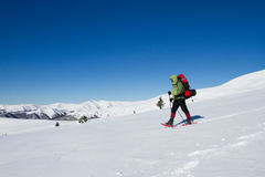 Winter hiking in the mountains on snowshoes with a backpack and tent. Stock Image