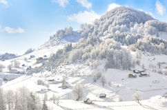 Winter hill landscape with houses and snowy trees Royalty Free Stock Photos