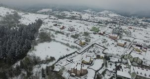 Winter hills slopes strewn with snow. Snowy village. Aerial view stock footage