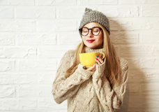 Winter Hipster Girl Enjoying a Cup of Hot Tea. Romantic Winter Hipster Girl in Knitted Sweater and Beanie Hat Enjoying a Cup of Hot Tea or Coffee in Hands Royalty Free Stock Images