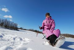 Winter hobby. Young attractive girl on winter fishing Royalty Free Stock Image