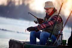 Winter hobby -elderly man fishing. On lake Stock Photography