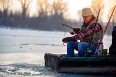 Winter hobby - fisherman fishing on the frozen lake. Winter hobby – smiling fisherman fishing on the frozen lake Stock Images