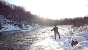 Winter hobby. Man fishing trout in forest river stock footage