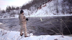 Winter hobby. Man fishing trout in forest river stock video footage
