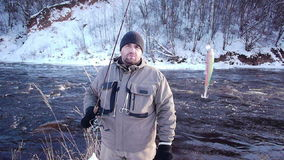 Winter hobby. Man fishing trout in forest river stock video