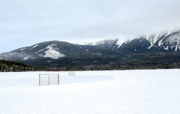 Winter Hockey. Rink set on a lake in the mountains Royalty Free Stock Photo