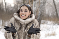Winter holiday. The smiling girl in a fur coat Stock Images