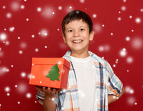 Winter holiday christmas concept - boy with box gift on red back Royalty Free Stock Photography