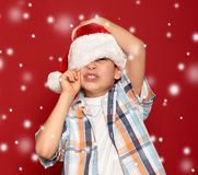 Winter holiday christmas concept - boy in santa hat close one ey Royalty Free Stock Photos