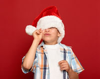 Winter holiday christmas concept - boy in santa hat close one eye on red Stock Photography