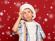 Winter holiday christmas concept - boy in santa hat have idea on Stock Image