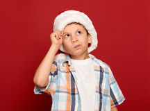 Winter holiday christmas concept - boy in santa hat have idea on red background Royalty Free Stock Photo