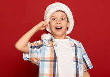 Winter holiday christmas concept - boy in santa hat have idea on red background Stock Images