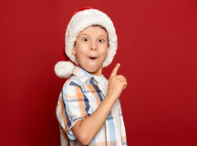 Winter holiday christmas concept - boy in santa hat have idea on red background Stock Photography