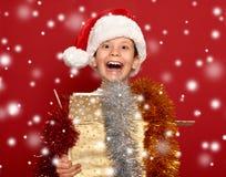 Winter holiday christmas concept - boy in santa hat having fun o Stock Photo