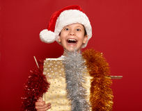 Winter holiday christmas concept - boy in santa hat having fun on red Royalty Free Stock Photos