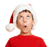 Winter holiday christmas concept - boy in santa hat look up on white isolated Stock Photography