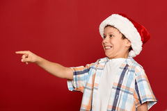 Winter holiday christmas concept - boy in santa hat point his finger on red Royalty Free Stock Photography