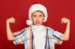 Winter holiday christmas concept - boy in santa hat show muscle on red Royalty Free Stock Photos