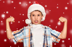 Winter holiday christmas concept - boy in santa hat show muscle Stock Image