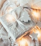 Winter holiday Christmas decorations, white gift boxes and knitt. Ed sweater with warm string lights royalty free stock images