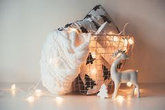 Winter holiday Christmas home decorations, white gift box and kn. Itted sweater in basket with warm string lights royalty free stock image