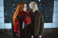 Winter holiday, dating, urban fashion and relationship concept. Stylish hipsters couple standing in the winter street.  stock photography