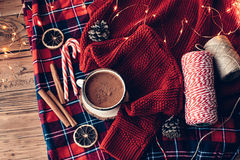 Winter holiday decor. Winter homely scene. Warm knit sweater, plaid blanket and cup of hot cocoa. Christmas lollipop, cinnamon and other holiday decor Stock Photography