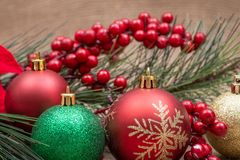 Winter holiday decoration: Blooming Holiday Red Poinsettia, Pine, Berry bush and Christmas tree balls on burlap. Background stock photos