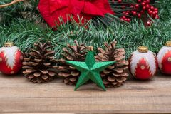 Winter holiday decoration: Blooming Red Poinsettia, Pine, Berry bush, Christmas tree balls, pine cone, green star and garland. On wooden background stock photography