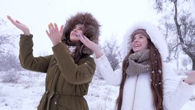 Winter holiday, emotional people put arms under snow and laughing. On nature stock video