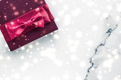 Winter holiday gifts with cherry silk bow and glowing snow on frozen marble background, Christmas presents surprise. New Years Eve celebration, wrapped luxury royalty free stock photo