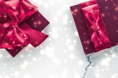 Winter holiday gifts with cherry silk bow and glowing snow on frozen marble background, Christmas presents surprise. New Years Eve celebration, wrapped luxury royalty free stock photography