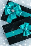 Winter holiday gifts with emerald silk bow and glowing snow on frozen marble background, Christmas presents surprise. New Years Eve celebration, wrapped luxury royalty free stock image