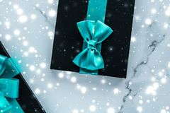 Winter holiday gifts with emerald silk bow and glowing snow on frozen marble background, Christmas presents surprise. New Years Eve celebration, wrapped luxury stock photography