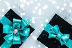 Winter holiday gifts with emerald silk bow and glowing snow on frozen marble background, Christmas presents surprise. New Years Eve celebration, wrapped luxury stock photos
