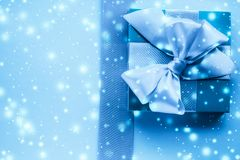 Winter holiday gifts and glowing snow on frozen blue background, Christmas presents surprise. New Years Eve celebration, wrapped luxury boxes and cold season stock photography
