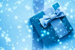 Winter holiday gifts and glowing snow on frozen blue background, Christmas presents surprise. New Years Eve celebration, wrapped luxury boxes and cold season royalty free stock image