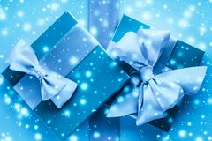 Winter holiday gifts and glowing snow on frozen blue background, Christmas presents surprise. New Years Eve celebration, wrapped luxury boxes and cold season stock image
