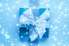 Winter holiday gifts and glowing snow on frozen blue background, Christmas presents surprise. New Years Eve celebration, wrapped luxury boxes and cold season stock photos
